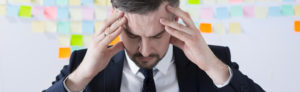 A businessman holds his head in his hands